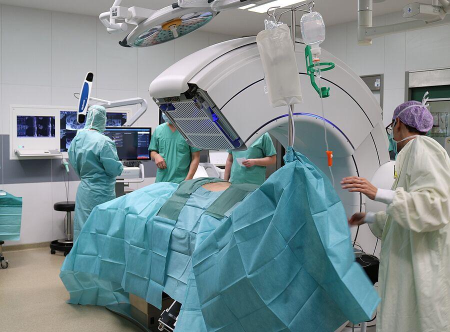 Der O-Arm umschließt den Patienten und erlaubt somit zwei- und dreidimensionale Aufnahmen sowie die Durchleuchtung (Fluoroskopie) des Körpers während der Operation, ohne dass dessen Liegeposition verändert werden muss.