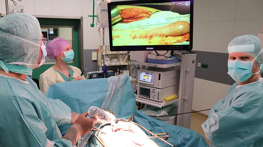 Wo genau befindet sich die Resektionsgrenze? Bei dieser Magen-OP nutzen Prof. Dr. med. Karsten Ridwelski (links) und Oberarzt Dr. med. Tino Hoepfner die ICG-Technik. Wegen eines Tumorleidens wurde die Speiseröhre entfernt. Damit der Patient weiterhin essen und trinken kann, wurde aus einem Teil des Magens ein Ersatz geschaffen. Mittels der ICG-Technik prüfen die Operateure hier im Bildschirm die Resektionsgrenze des sogenannten Magenschlauchs.